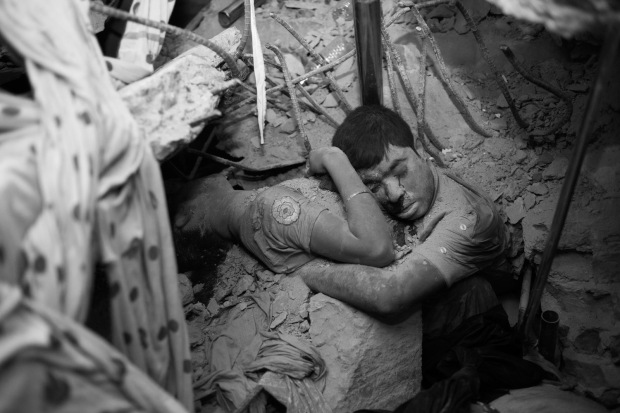 03_Garment Workers in Deathtrap_ Taslima Akhter_ Nobody knows who are they, what is the relation between them but the crude reality make them closer and may be they are trying to save each other and the last moment of their life from the death trap of Savar Rana Plaza_. Embrace in Death. Near about 438 workers died as building Collapse at Savar Rana Plaza. Most of them are women. Savar Dhaka, Bangladesh, 24th April 2013